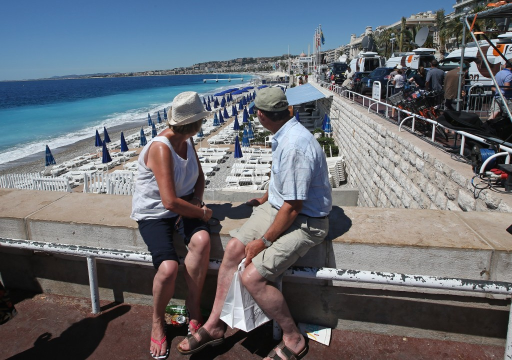 People sit overlooking the beach and not far from the site of the truck attack in the French resort city of Nice, southern France, Friday, July 15, 2016. France has been stunned again as a large white truck killed many people after it mowed through a crowd of revelers gathered for a Bastille Day fireworks display in the Riviera city of Nice. (AP Photo/Luca Bruno)