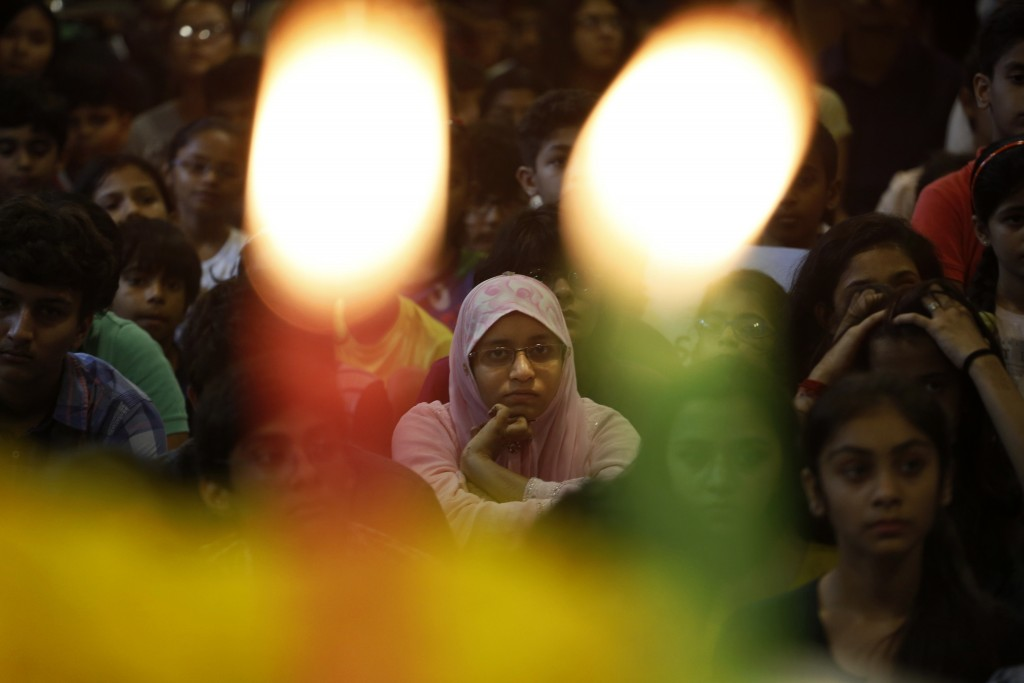 Indian school children attend a prayer ceremony in memory of victims of a truck attack in France, at a school in Ahmadabad, India, Friday, July 15, 2016. A large truck mowed through revelers gathered for Bastille Day fireworks in Nice, killing dozens of people and sending people fleeing into the sea as it bore down for more than a mile along the Riviera city's famed waterfront promenade. (AP Photo/Ajit Solanki)