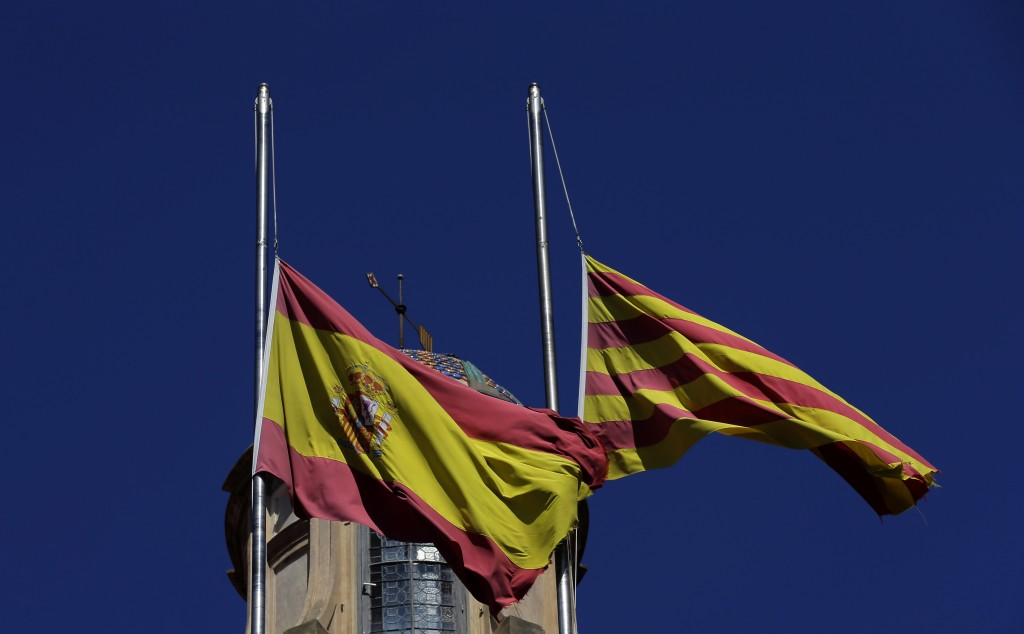Spanish flag, left, and Catalan flag at half staff in honor for the victims of the Bastille Day tragedy in Nice, France, atop a building in Barcelona, Spain, Friday, July 15, 2016. World leaders are expressing dismay, sadness and solidarity with France over the attack carried out by a man who drove a truck into crowds of people celebrating France's national Bastille Day in Nice. (AP Photo/Manu Fernandez)