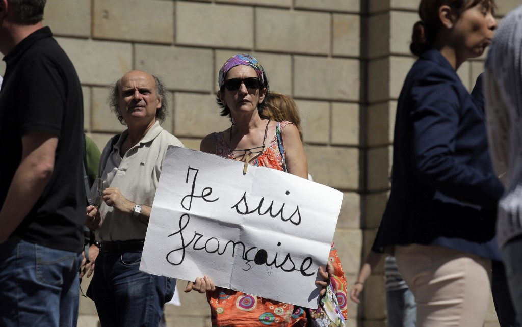 A woman holds a banner during a minute of silence in honor of the victims of the Bastille Day tragedy in Nice, in Barcelona, Spain, Friday, July 15, 2016. World leaders are expressing dismay, sadness and solidarity with France over the attack carried out by a man who drove truck into crowds of people celebrating France's national day in Nice. (AP Photo/Manu Fernandez)