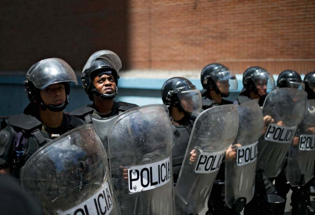 A police officer looks up at protesters on top of a building, as he helps block demonstrators from a National Electoral Council (CNE) office in Los Teques on the outskirts of Caracas, Venezuela, Wednesday, Sept. 7, 2016. Venezuelans are marching in cities across the country to demand authorities allow a recall referendum against President Nicolas Maduro to go forward this year. (AP Photo/Ariana Cubillos)