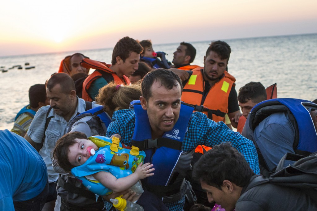 FILE - In this Aug. 13, 2015 file photo, a man carries a girl in his arm as they arrive with other migrants just after dawn on a dinghy after crossing from Turkey to the island of Kos in southeastern Greece. The question of what to do about the world's 65.3 million displaced people takes center stage at the United Nations General Assembly Monday, Sept. 19, 2016, when leaders from around the globe converge on New York for the first-ever summit on Addressing Large Movements of Refugees and Migrants. (AP Photo/Alexander Zemlianichenko, File)