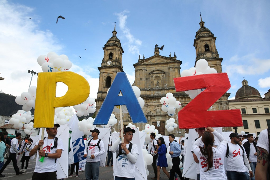 """People hold up letters that form the word """"Peace"""" in Spanish during a gathering at Bolivar square in Bogota, Colombia, Monday, Sept. 26, 2016. Colombia's government and the Revolutionary Armed Forces of Colombia signed a peace agreement to end over 50 years of conflict, in Cartagena. (AP Photo/ Jennifer Alarcon)"""