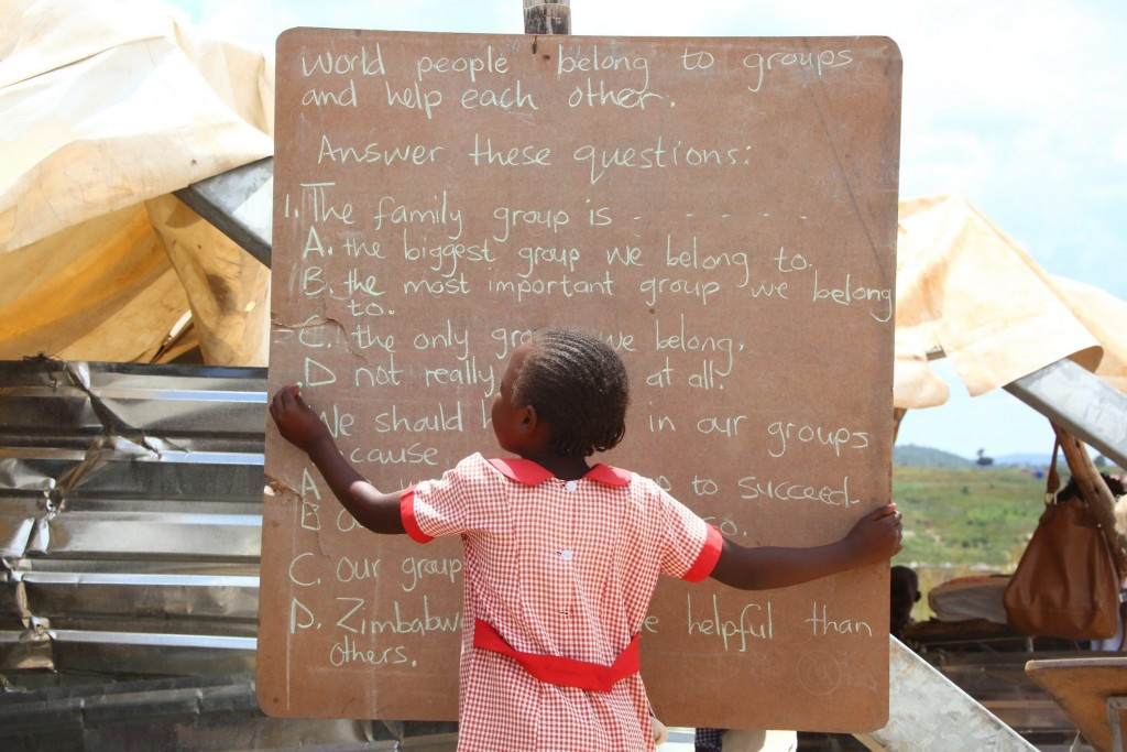 epa05211323 A primary school girl writes on a board at the Eastview School in Caledonia, Harare, Zimbabwe, 14 March 2016. Students most of whom their parents are low income earners and informal traders, learn under very poor facilities. EPA/AARON UFUMELI