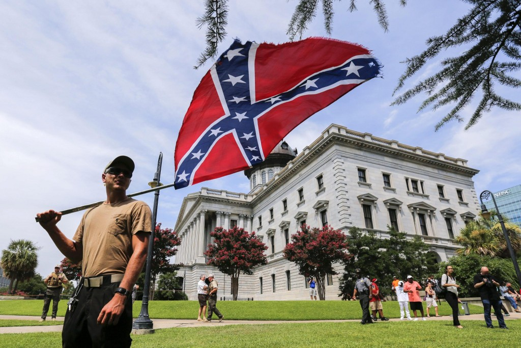 epa04852427 A man displays a Confederate battle flag during New Black Panther Party and Ku Klux Klan rallies on the grounds of the South Carolina Capitol in Columbia, South Carolina, USA, 18 July 2015. EPA/ERIK S. LESSER