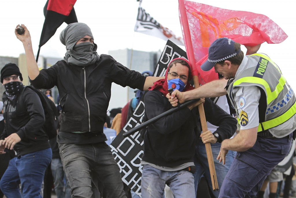 Demonstrators clash with military police during a protest against the approval of the measure to cap government spending over the next 20 years, in Brasilia, Brazil, Tuesday, Dec. 13, 2016. Congress in Brazil approved the spending cap measure that was opposed by many sectors but justified as way to revive a struggling economy. (AP Photo/Eraldo Peres)