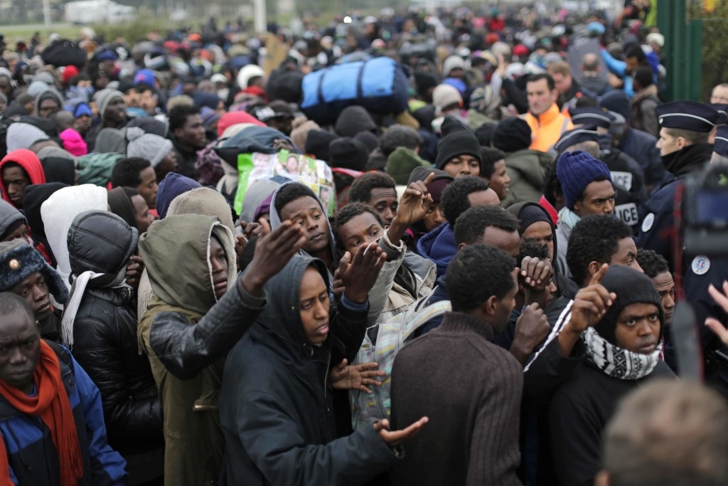 """Migrants line-up to register at a processing center in the makeshift migrant camp known as """"the jungle"""" near Calais, northern France, on Oct. 24, 2016. The French evacuated 6,400 migrants from the encampment in 170 buses, starting on Oct. 24, with the intent of resettling them in different regions of France. On Oct. 26 French authorities announced that the camp had been cleared. (AP Photo/Emilio Morenatti)"""