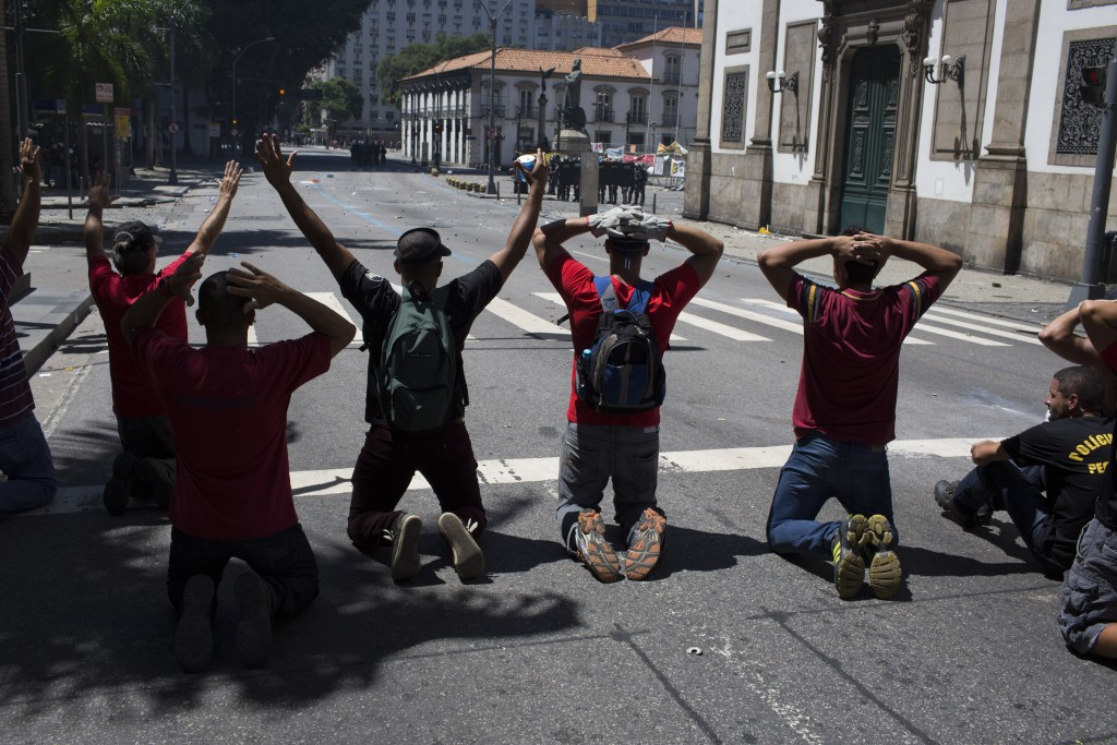 Protesters kneel on the opposite side of the street from police during clashes outside the state legislature where lawmakers are discussing austerity measures in Rio de Janeiro, Brazil, Tuesday, Dec. 6, 2016. Legislators were voting on measures to address the state's deepening financial crisis, in which thousands of state employees and retirees have not been paid or have been paid months late. (AP Photo/Leo Correa)
