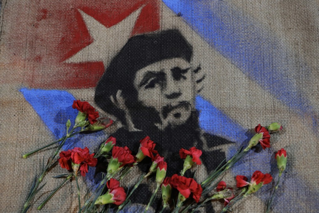 Flowers placed by members of Mexico's communist party lay on an image of late Cuban President Fidel Castro, outside the Cuban embassy in Mexico City, late Saturday, Nov. 26, 2016. Castro, who led a rebel army to improbable victory in Cuba, embraced Soviet-style communism and defied the power of 10 U.S. presidents during his half century rule, died in Cuba on Friday at age 90. (AP Photo/Rebecca Blackwell)