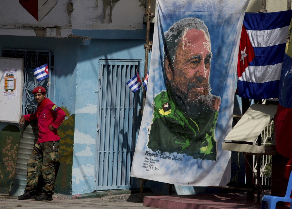A Venezuelan militia member stands next a banner of Fidel Castro in the 23 de Enero neighborhood of Caracas, Venezuela, Saturday, Nov. 26, 2016. Castro, who led a rebel army to improbable victory, embraced Soviet-style communism and defied the power of 10 U.S. presidents during his half century rule of Cuba, died at age 90 late Friday, Nov. 25. (AP Photo/Fernando Llano)