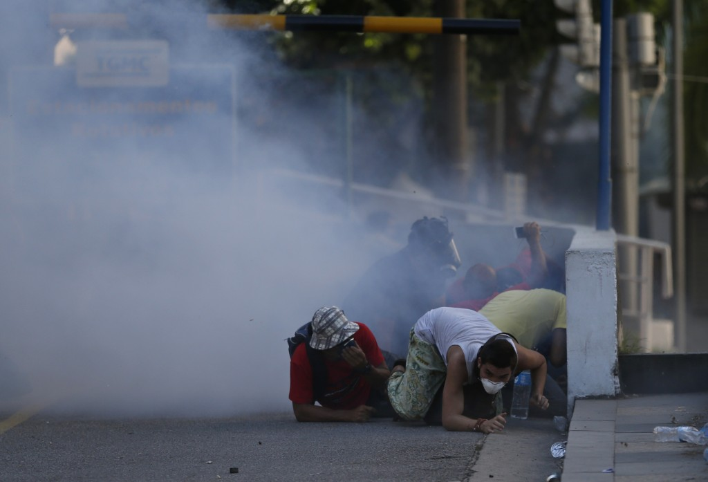 Demonstrators seek cover from teargas in clashes with police outside the state legislature during a protest against austerity measures being discussed in the chamber, in Rio de Janeiro, Brazil, Tuesday, Dec. 6, 2016. Legislators were voting on measures to address the state's deepening financial crisis, in which thousands of state employees and retirees have not been paid or have been paid months late. (AP Photo/Silvia Izquierdo)