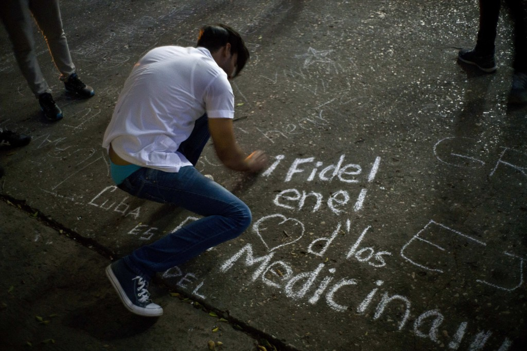 """A student writes on a sidewalk with chalk """"Fidel in the hearts of the med students"""" during a vigil for the late Cuban leader Fidel Castro at the university where Castro studied law as a young man in Havana, Cuba, Saturday, Nov. 26, 2016. Castro, who led a rebel army to improbable victory in Cuba, embraced Soviet-style communism and defied the power of U.S. presidents during his half century rule, died at age 90. (AP Photo/Ramon Espinosa)"""