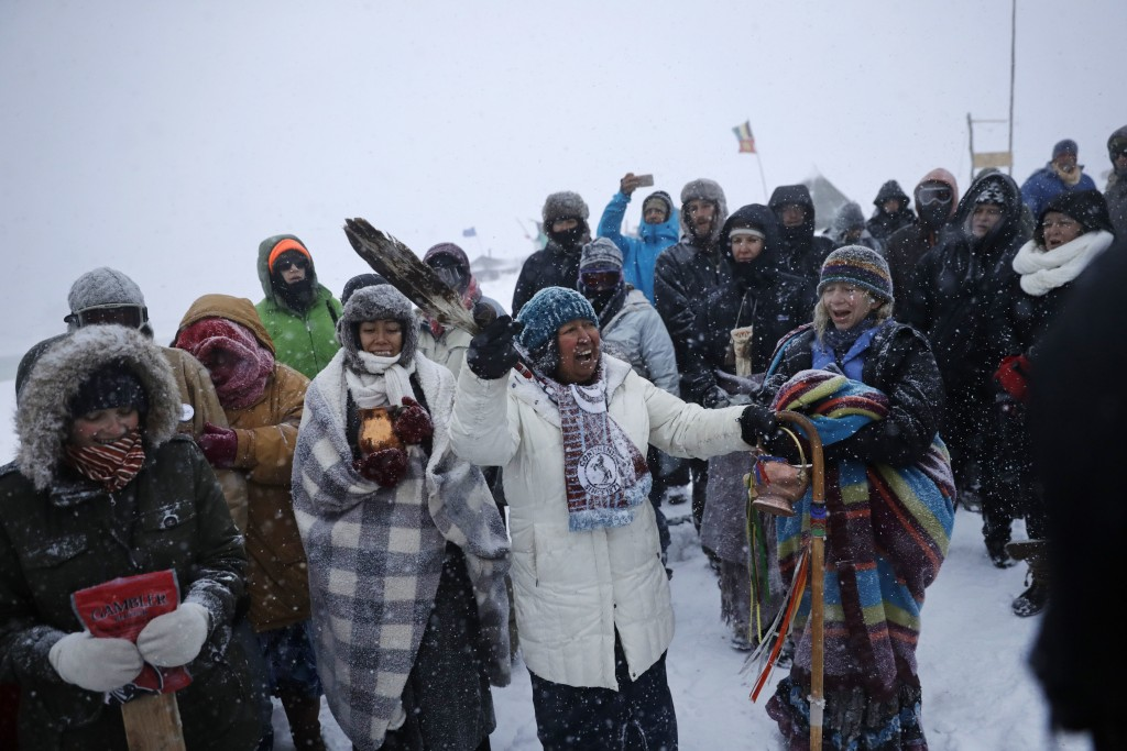 In this Tuesday, Nov. 29, 2016 photo, Beatrice Menase Kwe Jackson of the Ojibwe Native American tribe leads a song during a traditional water ceremony along the Cannonball river at the Oceti Sakowin camp where people have gathered to protest the Dakota Access oil pipeline in Cannon Ball, N.D. The pipeline is largely complete except for a short segment that is planned to pass beneath a Missouri River reservoir. The company doing the building says it is unwilling to reroute the project. (AP Photo/David Goldman)