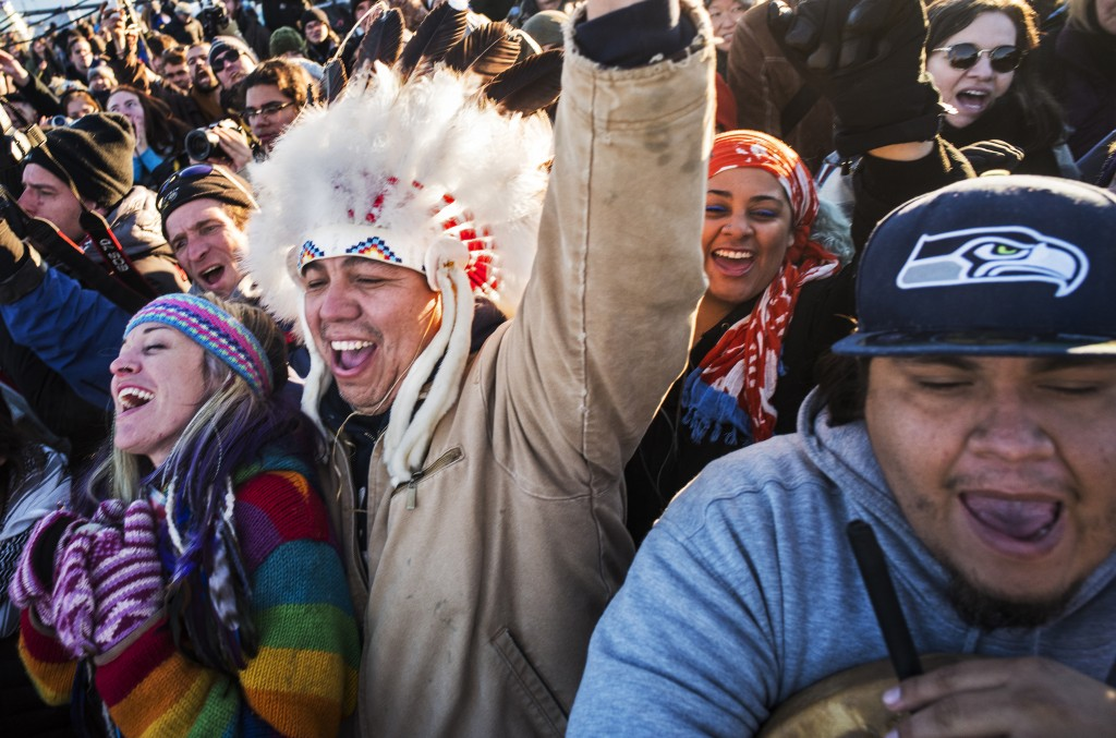 Katibunny Roberts and her husband, Lance King, of Kyle, S.D., celebrate the Army Corps' denial of an easement to bury a section of the Dakota Access pipeline under the Missouri River, Sunday, Dec. 5, 2016, in Cannon Ball, N.D. King recently moved back to his ancestral Lakota homeland. He is a descendant of Chief Matthew King, Noble Redman. On the right is Lazaro Tinoco of the Lower Elwha Klallam Tribe in Washington. (Richard Tsong-Taatarii/Star Tribune via AP)