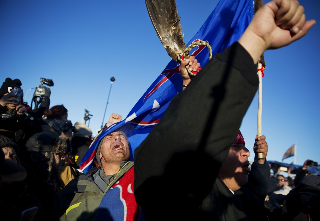 Members of a Native American drum procession celebrate at the Oceti Sakowin camp after it was announced that the U.S. Army Corps of Engineers won't grant easement for the Dakota Access oil pipeline in Cannon Ball, N.D., Sunday, Dec. 4, 2016. (AP Photo/David Goldman)
