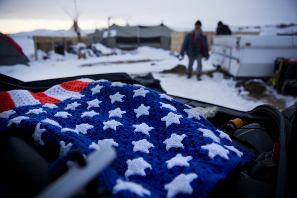 An American flag quilt lays in the back of a veteran's car at the Oceti Sakowin camp where people have gathered to protest the Dakota Access oil pipeline in Cannon Ball, N.D., Friday, Dec. 2, 2016. (AP Photo/David Goldman)