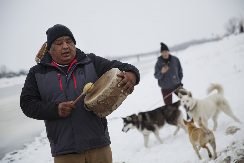 Dan Nanamkin, of the Colville Nez Perce tribe in Nespelem, Wash., drums a traditional song on the shore of the Cannonball River before a group arrives by boat at the Oceti Sakowin camp where people have gathered to protest the Dakota Access oil pipeline in Cannon Ball, N.D., Thursday, Dec. 1, 2016. (AP Photo/David Goldman)