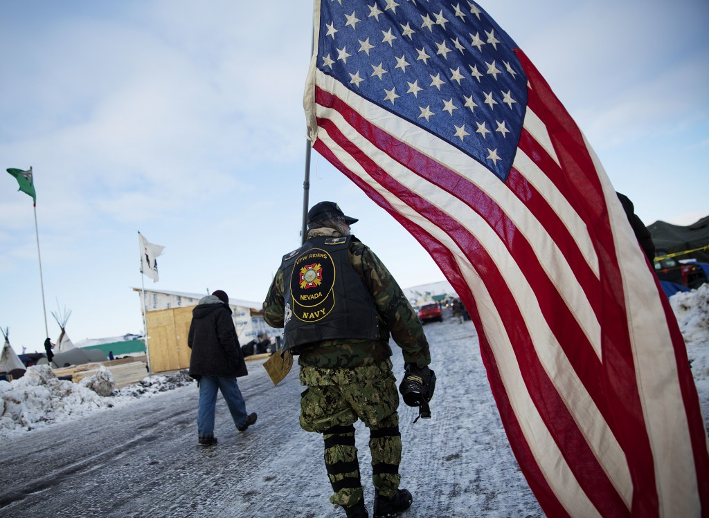Navy veteran Rob McHaney, of Reno, N.V., walks with an American flag at the Oceti Sakowin camp where people have gathered to protest the Dakota Access oil pipeline in Cannon Ball, N.D., Sunday, Dec. 4, 2016. Tribal elders have asked the military veterans joining the large Dakota Access pipeline protest encampment not to have confrontations with law enforcement officials, an organizer with Veterans Stand for Standing Rock said Sunday, adding the group is there to help out those who've dug in against the four-state, $3.8 billion project. (AP Photo/David Goldman)