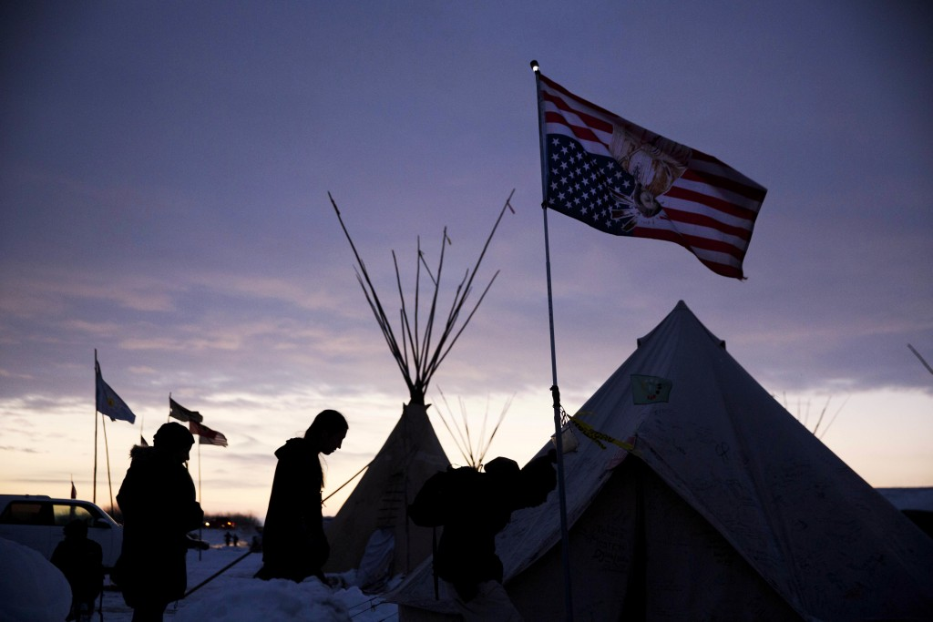 Travelers arrive at the Oceti Sakowin camp where people have gathered to protest the Dakota Access oil pipeline as they walk into a tent next to an upside-down american flag in Cannon Ball, N.D., Friday, Dec. 2, 2016. (AP Photo/David Goldman)