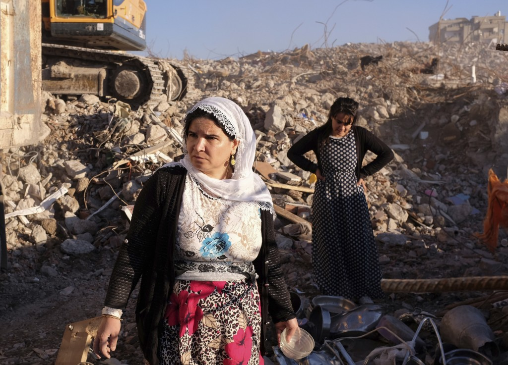 In this Saturday, Nov. 19, 2016 photo, residents stand around in the rubble of an area in Sirnak, southeastern Turkey, destroyed in government operations against Kurdish militants of the Kurdistan Workers Party or PKK. The 246-day curfew in the mainly-Kurdish city of some 290,000 was imposed on March 14 as part of government operations against PKK. (AP Photo/Cansu Alkaya)