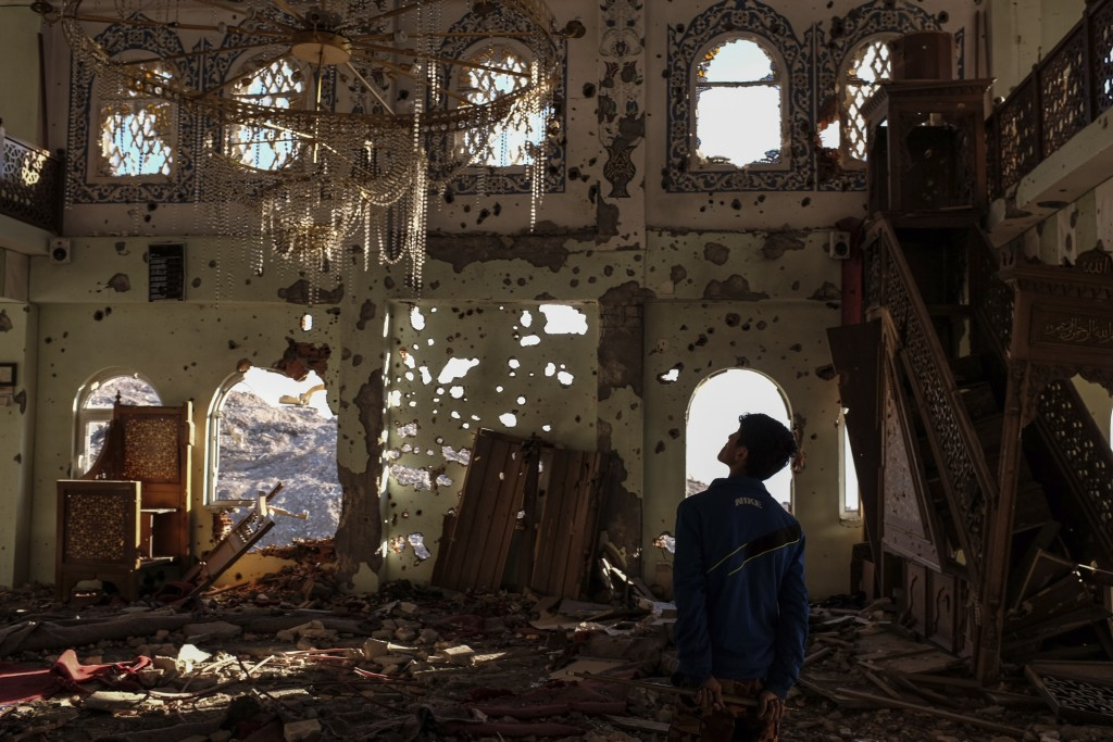 In this Saturday, Nov. 19, 2016 photo, residents look at the damage inside a mosque, in Sirnak, southeastern Turkey, destroyed in government operations against Kurdish militants of the Kurdistan Workers Party or PKK. The 246-day curfew in the mainly-Kurdish city of some 290,000 was imposed on March 14 as part of government operations against PKK. (AP Photo/Cansu Alkaya)