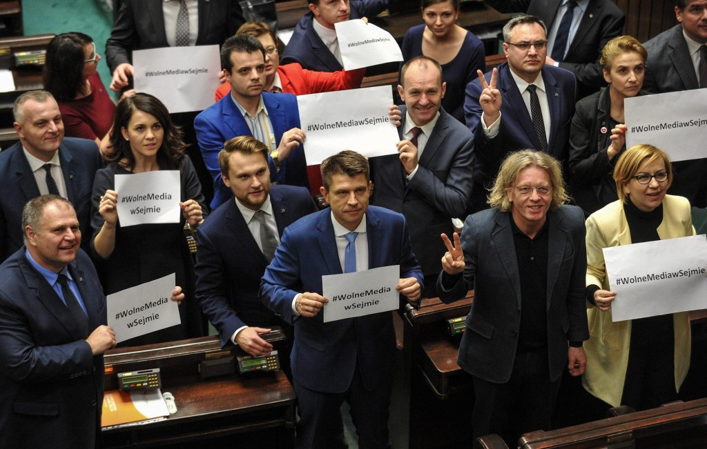 epa05678468 Opposition party Nowoczesna leader Ryszard Petru (C) with other parliamentarians hold a card ''#Free Media in Sejm' during a protest at the plenary session in Sejm, the lower house of the Polish parliament in Warsaw, Poland, 16 December 2016. Friday was announced 'A day without politicians by a group of Polish media due to planned changes in Sejm media regulations. Journalist and opposition politicians protest against planned further restrictions of access to the Sejm for reporters. The rules proposed by the Sejm Speaker Marek Kuchcinski limit the number of journalists allowed in the Sejm building. Contacts between media and parliamentarians will be only available in a media centre outside the main Sejm building. The rules are due to take effect in 2017. EPA/MARCIN OBARA POLAND OUT POLAND OUT